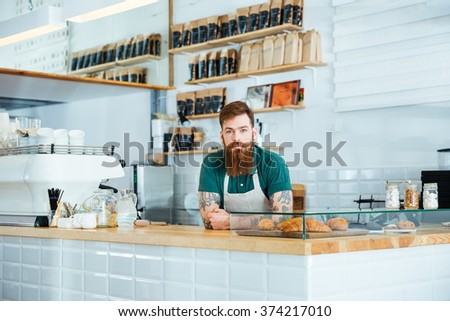 Serious attractive barista with beard and moustache standing in coffee shop - stock photo