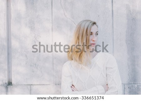 Serious attractive blond woman standing watching - stock photo