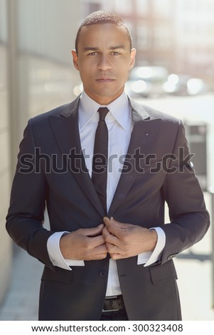 Serious attractive businessman walking down an urban street adjusting his suit jacket as he approaches the camera, close up upper body view - stock photo