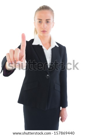 Serious attractive businesswoman pointing upwards on white background