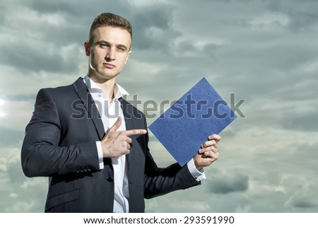 Serious attractive man in formal suit holding sheet of paper standing on blue sky background copyspace, horizontal picture - stock photo