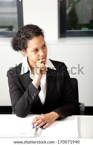 Serious attractive young African American businesswoman in a stylish suit sitting at a table in a meeting listening to a colleague with a thoughtful expression - stock photo