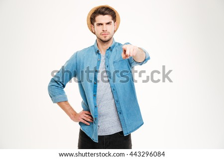 Serious attractive young man standing and pointing to camera over white background - stock photo