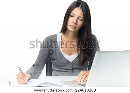 Serious attractive young woman working at a desk with her laptop computer writing notes in a notebook conceptual of a hardworking office worker or businesswoman, or a student studying by e-learning