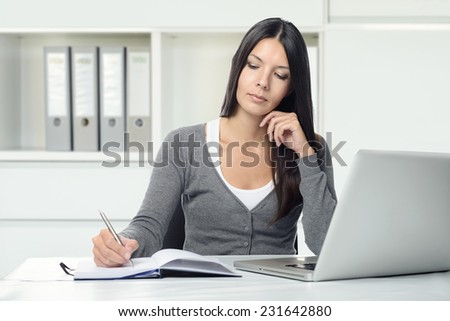 Serious attractive young woman working at a desk with her laptop computer writing notes in a notebook conceptual of a hardworking office worker or businesswoman, or a student studying by e-learning - stock photo