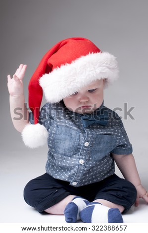 Serious baby boy wearing santa hat and denim shirt with bow tie.