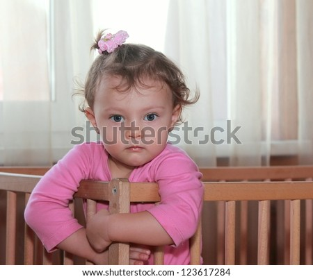 Serious baby girl in crib with thinking look in pink dress. Closeup portrait