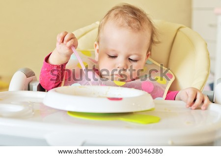 serious baby girl is eating - stock photo