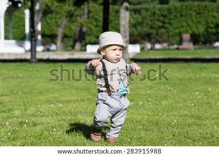 Serious baby walking in park in sunny weather.  - stock photo