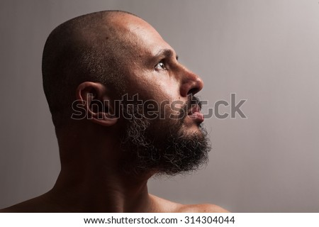 Serious bald man with beard in profile on dark studio background looking sides - stock photo