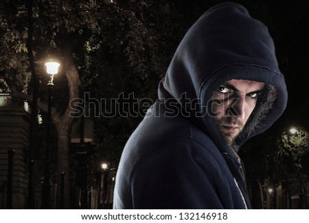 Serious bandit in ghetto at night looking to you - stock photo