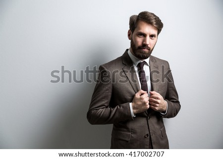 Serious bearded businessperson in suit standing against light grey. Mock up