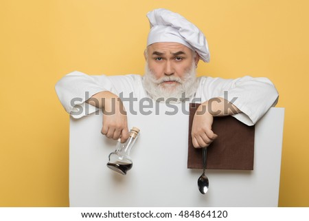 Serious bearded cook holding blank paper with spoon bottle and napkin on yellow background, copy space