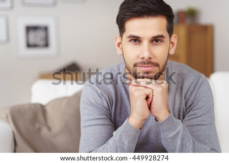 Serious bearded handsome young man relaxing on a sofa at home resting his chin on his hands staring intently at the camera - stock photo
