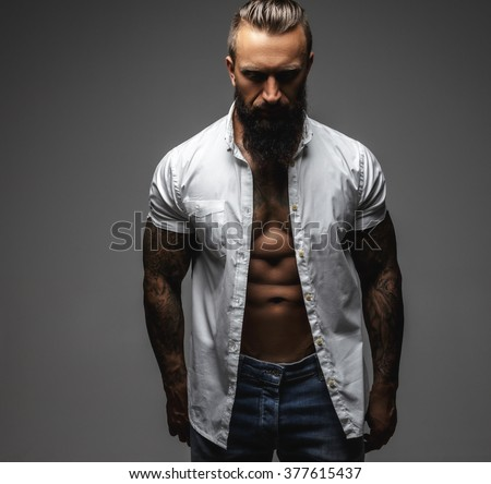 Serious bearded man with tattooes on his arms in a white shirt. Isolated on a grey background.