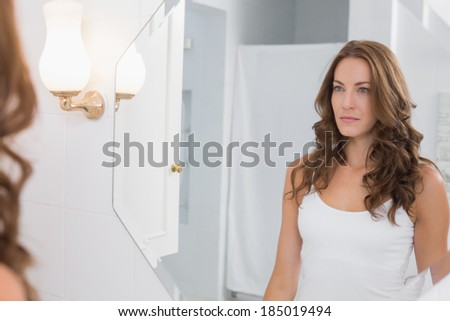 Serious beautiful young woman looking at herself in the bathroom mirror at home - stock photo