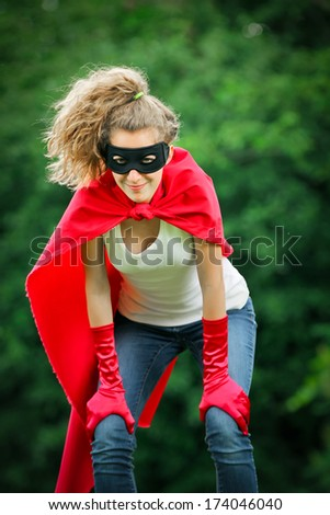 Serious blond and caucasian woman with a mask and red super hero kit