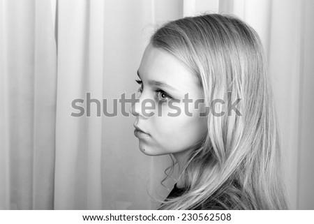 Serious blond Caucasian girl, monochrome studio profile portrait - stock photo