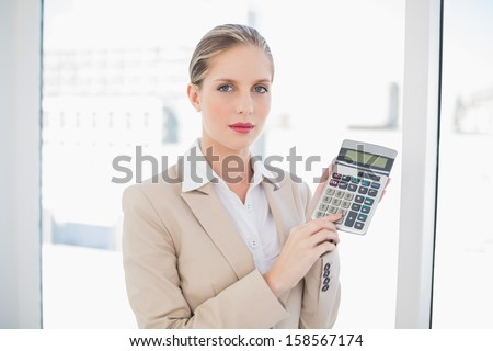Serious blonde businesswoman in bright office showing calculator
