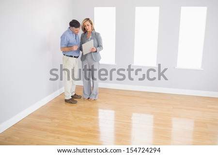 Serious blonde realtor showing an empty room and some documents to a potential mature buyer - stock photo