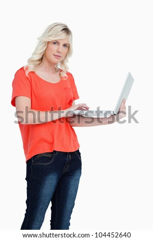 Serious blonde woman holding a laptop in her left hand against a white background - stock photo