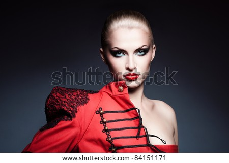 serious blonde woman in red jacket - stock photo