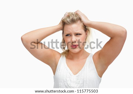 Serious blonde woman placing her hands on her head against a white background