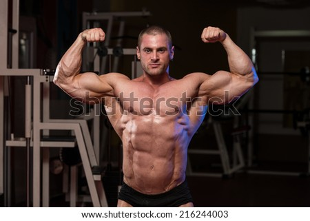 Serious Bodybuilder Standing In The Gym And Flexing Muscles