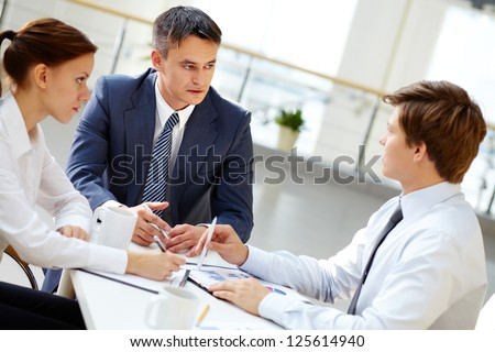 Serious boss looking at one of his employees and listening to him at meeting - stock photo