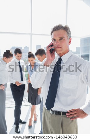 Serious boss on the phone standing in a modern office with colleagues behind - stock photo