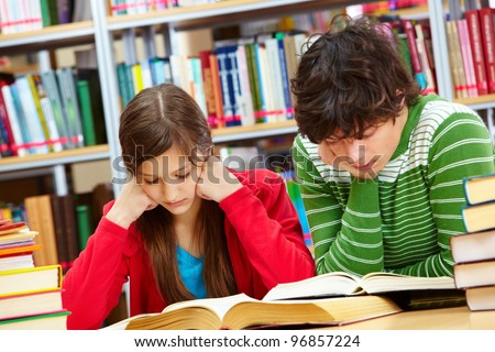 Serious boy and girl reading books at library - stock photo