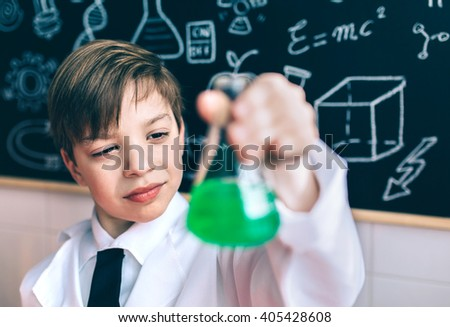 Serious boy looking flask with chemical liquid - stock photo