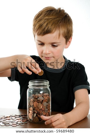 Serious Boy Putting Money in Glass Jar - stock photo