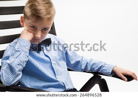 Serious boy schoolboy shirt sitting on a chair - stock photo