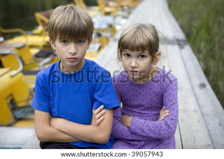serious brother and sister sitting on piers - stock photo