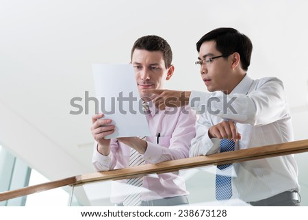 Serious business colleagues reading document - stock photo