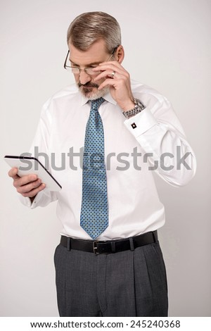 Serious business executive looking his digital tablet  - stock photo