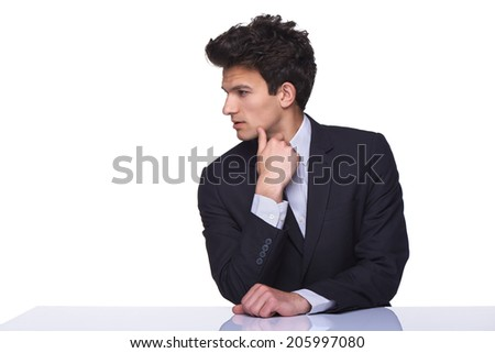 Serious business man sitting on table with hand on chin looking to the side, over white background - stock photo