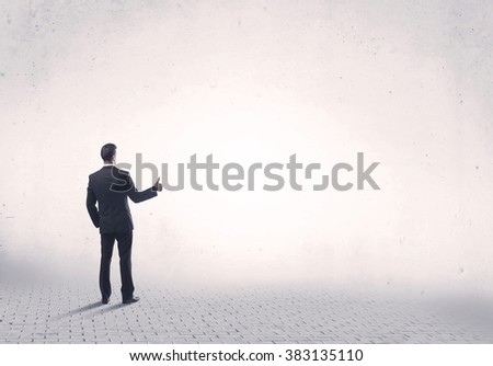 Serious business man standing on grey brick floor and thinging about decisions concept - stock photo