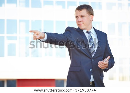 Serious business man with a mobile phone shows his hand to the side. Man shows hand side. Point with a finger.