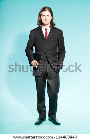 Serious business man with long brown hair holding tablet. Wearing black striped suit and dark red tie. Standing out guy. Isolated on light blue background. Studio shot.