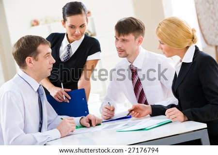 Serious business partners looking at their boss explaining new plan