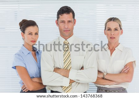 Serious business people in office looking at camera - stock photo