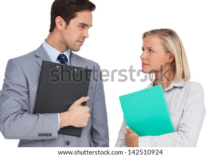 Serious business people looking at each other with folders on white background - stock photo