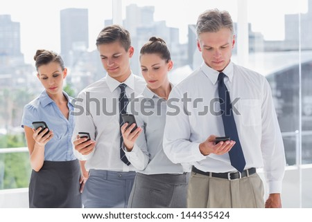 Serious business people standing together in line with their mobile in a modern office - stock photo