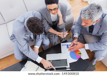 Serious business people using laptop and working together on sofa at office - stock photo