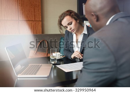 Serious business people working together in a cafe and reading some contract documents. Businessman and businesswoman discussing paperwork at table. - stock photo