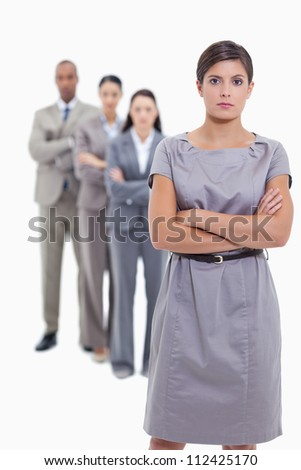 Serious business team crossing their arms and standing behind each other with focus on the foreground woman against white background - stock photo