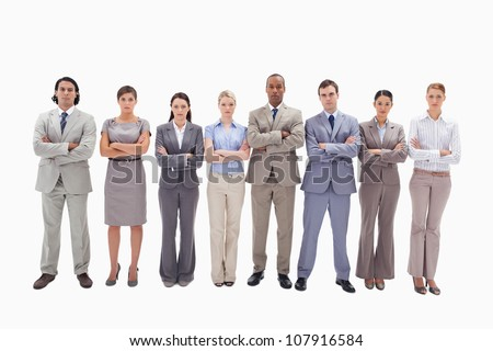 Serious business team crossing their arms side by side against white background - stock photo