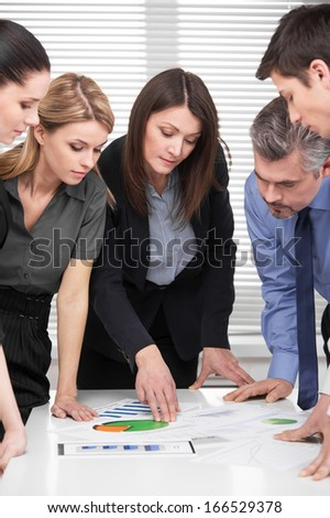 Serious business team having brainstorm in modern office. Adult attractive business woman leading group of business people  - stock photo